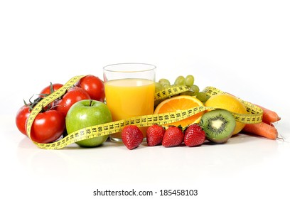 macro vegetables as tomatoes and carrots with fruit as grapes and apple wrapped in measure tape in diet , weight loss and healthy nutrition concept isolated on white background