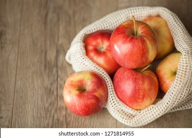 Macro view of a group of organic Gala apples in a reusable produce bag on wooden table.