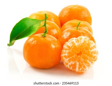 Macro view of group of ripe tangerine with green leaf isolated on white background