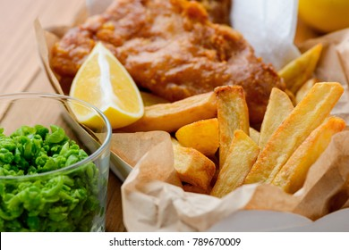 Macro view on green peas, fish and chips. British lunch concept. Easy and tasty way to still your hunger.