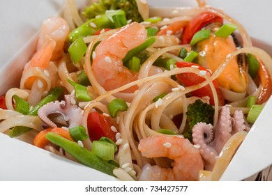 Macro view on wok noodles with octopuses, mussels, shrimps, broccoli, pepper, lettuce, asparagus and sesame seeds in soy sauce. Asian take-out food.