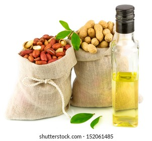 Macro view of purified and raw peanut in flax sack and glass bottle of oil with leaves isolated on white background