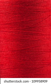 Macro view of red thread wound on a spool