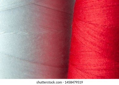 macrophotography of overlock thread on large spools in white and red color