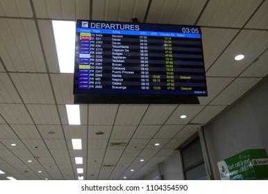 MACTAN ISLAND, CEBU, PHILIPPINES--MARCH 2018: Upward shot of the departures flight status board at the Mactan-Cebu International Airport.