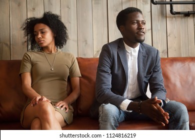Mad African American husband and wife ignoring each other, not talking, millennial couple in fight sitting apart on couch not ready to compromise, stubborn spouses cannot make peace, break up concept