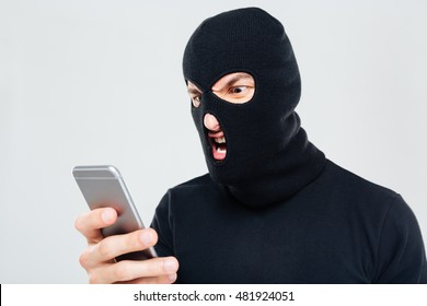 Mad aggressive young man in balaclava standing and using mobile phone
