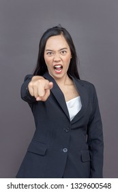 mad asian lady with business uniform suite point action or command in formal dress on isolated background