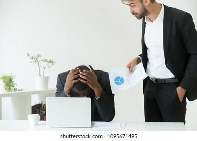Mad Caucasian employer yelling at depressed African American worker, blaming for business failure and documents mistake, humiliating black subordinate. Concept of work discrimination, demonization