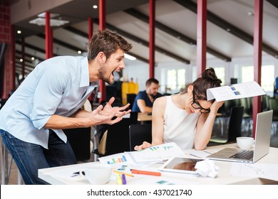Mad crazy young businessman arguing with sad stressed businesswoman at work in office