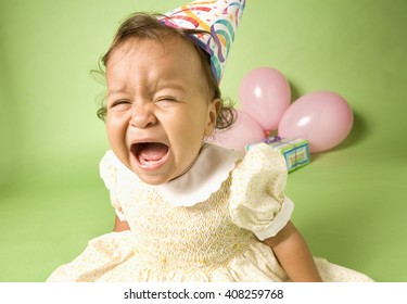Mad, crying baby in a party hat and dress crying in front of pink balloons and a present on a green background / It's My Party and I'll Cry If I Want To