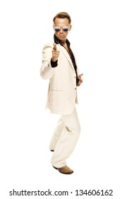 Mad disco dancer in white suit and snake leather boots pointing with his finger towards camera