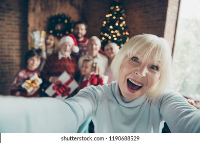 Mad funny funky granny grandma. Self-portrait of cheerful ecstatic grey-haired grandma. Noel gathering. grandparents grandchildren, sister, brother, son, daughter at house party, meeting near fir tree