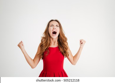 Mad furious young woman with raised hands standing and screaming over white background