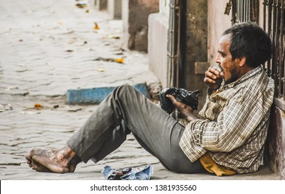 A mad hungry beggar is sitting on a road and trying to eat rotten food on the street of kolkata, west bengal, India in the month of march, 2019