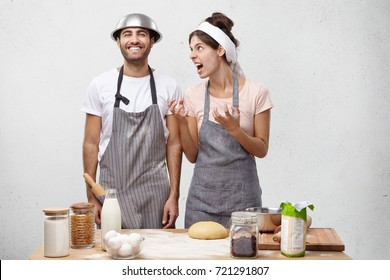 Mad loony housewife shoutes at lazy husband who foolishes at kitchen, doesn`t help to prepare dinner, made bad mistake and interrupts her by asking stupid questions. Couple has conflict at kitchen