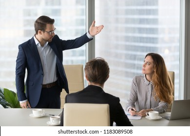Mad male worker gesturing asking female colleague leave business meeting, angry businessman standing showing to doors having dispute with woman partner, associates argue at negotiations