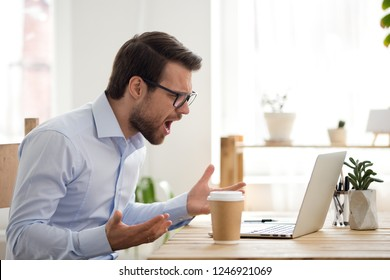 Mad male worker lose temper scream loudly having computer problems or virus attack, furious man shout experience laptop breakdown or data loss while working, angry employee get error message on pc