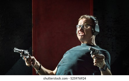Mad man in a headphones with a gun in his hand on the dark background