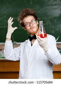 Mad professor in glasses admires his experimental red liquid