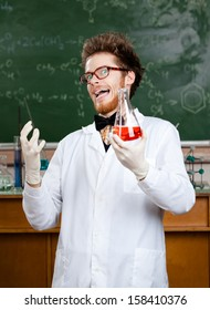 Mad professor laughs handing conical flask with red liquid in his laboratory