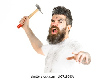 Mad repairman concept. Builder, plasterer, repairman, foreman attaks with hammer in hand, white background. Man with shouting face looks mad. Man with beard in dirty dusty shirt.