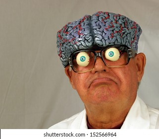 Mad scientist, with brain coming out of his head, makes a funny face as he ponders his problems.