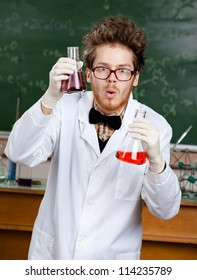 Mad scientist shows two flasks with colored liquid in his laboratory