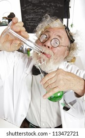 Mad senior scientist in lab concentrates on pouring green liquid into beaker. Frizzy grey hair, round glasses, lab coat, blackboard, vertical, high key, copy space.