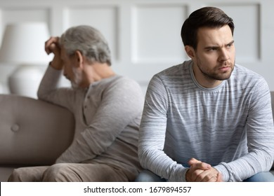 Mad thoughtful young man sit separately having fight misunderstanding with elderly father, angry stubborn mature dad and grown-up adult son avoid talking after quarrel, generation gap concept