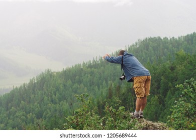 Mad tourist on mountain peak. Joyful traveler dives into abyss under rain. Crazy man is jumping on rocky summit. Positive person in flight over precipice. Exciting moment. Freedom in highlands.