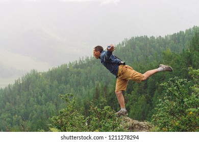 Mad tourist on mountain peak. Joyful traveler stands on one leg over abyss. Crazy man is jumping on rocky summit. Positive person in flight over precipice. Exciting rainy moment. Freedom in highlands.