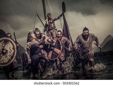 Mad vikings warriors in the attack, running along the shore with Drakkar on the background.
