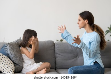 Mad young mom an little daughter sit on couch have fight arguing gesturing, furious angry mother yell dispute with preschooler girl, annoyed parent lecture small child imitating play pretend similar