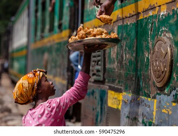 madagascar, africa, september 23, 2016: unknown sales woman offering homemade food to travelers in a train station Manakara