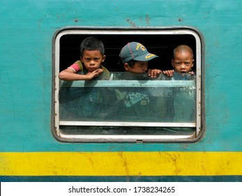 MADAGASCAR, octobre 7, 2008: Three young children inside the FCB train, the only railway in the country between Fiana and Manakara, they look outside the train through the window., Indian Ocean.