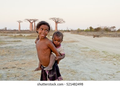 Madagascar-shy and poor african girl with infant on her back - poverty