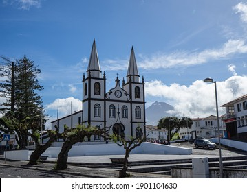 Madalena, Portugal - March 9, 2020: The church of Santa Maria Madalena and Portugals highest mountain, the Montanha do Pico in the background.