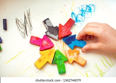 made homemade wax pencils from the wreckage of old crayons by melting them in the oven at high temperature in silicone form. crayons in the form of arrows lie on paper, hand child