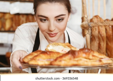 Made with love. Beautiful young female baker placing freshly baked croissants to the showcase