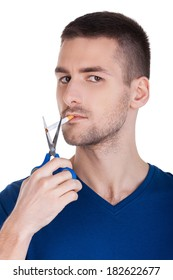 I made my decision. Confident young man holding scissors near the cigarette while standing isolated on white background