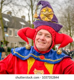 MADE, NETHERLANDS - FEBRUARY 11, 2018: Outdoor portrait of an unidentified smiling man dressed in a colorful jester's suit and with a jester's hood on his head; it is carnival in the village of Made.