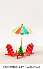 Made from paper Christmas tree, beach chair and umbrella in the sand. White background