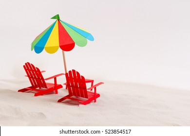 Made of paper umbrella and beach chair on the sand. White background