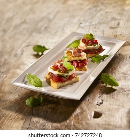 Made from Re-Plated Waste - Canapes with green leaves on white rectangle plate, light wood background, angled view.