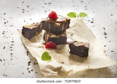 Made from Re-Plated Waste food – Chocolate fudge brownies with caramel syrup and raspberries on paper plating, angled view