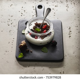 Made from Re-Plated Waste food – Creamy dessert pudding with forest fruits and cereal flakes in a jar with stone plate, angled view