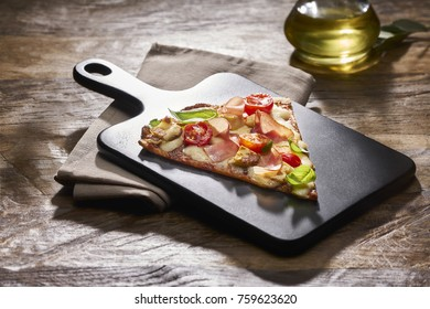 Made from Re-Plated Waste food – Fresh pizza slice, with tomatoes, basil, ham and mozzarella on gourmet plating in restaurant setting, angled view