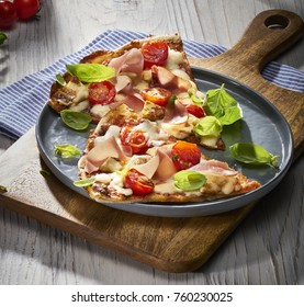 Made from Re-Plated Waste food – Fresh pizza slices, with tomatoes, basil, ham and mozzarella on gourmet plating in restaurant setting, angled view