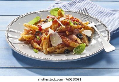 Made from Re-Plated Waste food - Fresh pasta with tomato sauce, bacon, parmesan, olives and herbs, gourmet restaurant plating, angled view